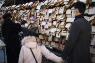"A girl with her family members hangs her ""ema"" board with her wish written on it in Yushima Tenmangu shrine in Tokyo on New Year's Day, Friday, Jan. 1, 2021. (AP Photo/Hiro Komae)"