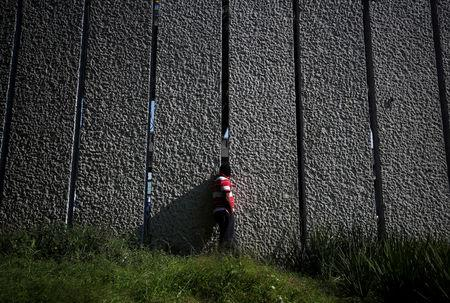 A migrant, part of a caravan of thousands traveling from Central America en route to the United States, looks out to the city through a wall from inside a makeshift camp in Mexico City, Mexico, November 7, 2018. REUTERS/Hannah McKay