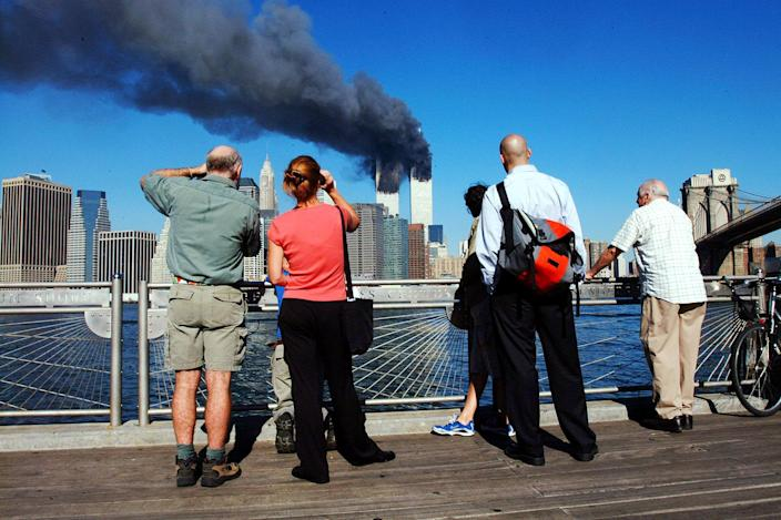 <p>Pedestrians on the waterfront in Brooklyn, New York, look across the East River to the burning World Trade Center towers Sept.11, 2001, after the terrorist attacks. (Photo: Henny Ray Abrams/AFP/Getty Images) </p>