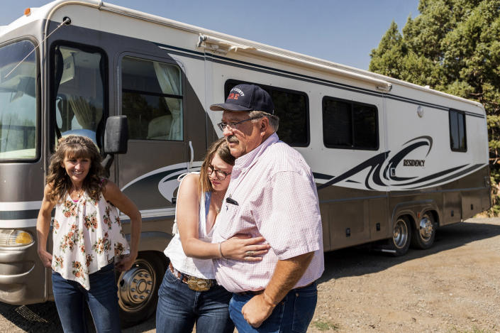 Paul Roen gets a hug from daughter Aubree Roen, 16, as his family donates their motorhome to EmergencyRV.org, Sunday, Sept. 5, 2021, in Sierra County, Calif. At left is his wife, Sheri Roen. (AP Photo/Noah Berger)
