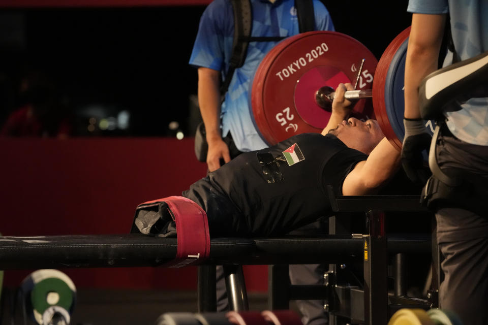 FILE - In this Aug. 26, 2021, file photo, Jordan's Omar Sami Hamadeh Qarada prepares to lift during men's 49kg powerlifting final at the Tokyo 2020 Paralympic Games in Tokyo, Japan. Qarada won a gold medal in the event. There are 4,403 Paralympic athletes competing in Tokyo, each with unique differences that have to be classified. Lines have to be draw, in the quest for fairness, to group similar impairments, or impairments that yield similar results. (AP Photo/Kiichiro Sato, File)