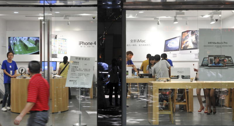A man walks past windows of a shop masquerading as a bona fide Apple store in downtown Kunming, in southwest China's Yunnan province, Thursday, July 21, 2011. China, long known for producing counterfeit consumer gadgets, software and brand name clothing, has reached a new piracy milestone - fake Apple stores. (AP Photo)  CHINA OUT
