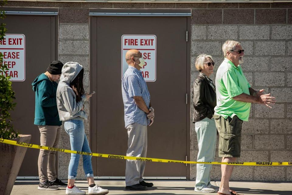 Shoppers practicing social distancing lined up outside retail warehouse store in Tucson during the coronavirus pandemic