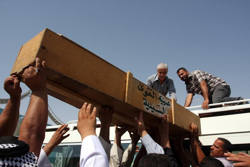 Family members of Khalaf Mohsen, 38, load his coffin onto a vehicle before burial in the Shiite holy city of Najaf, 100 miles (160 kilometers) south of Baghdad, Iraq, Tuesday, July 24, 2012. The man was killed when violence shook more than a dozen Iraqi cities Monday, killing more than 100 people in coordinated bombings and shootings and wounding twice as many in the country's deadliest day in more than two years. (AP Photo/Alaa al-Marjani)