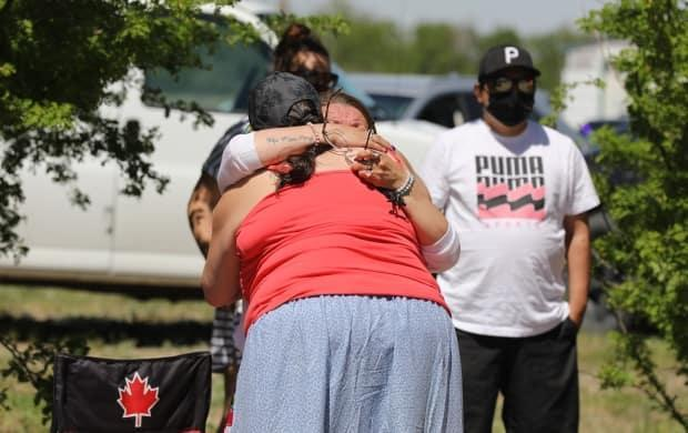 Attendees embrace each other during a prayer vigil on  the Muskowekwan First Nation on Tuesday.