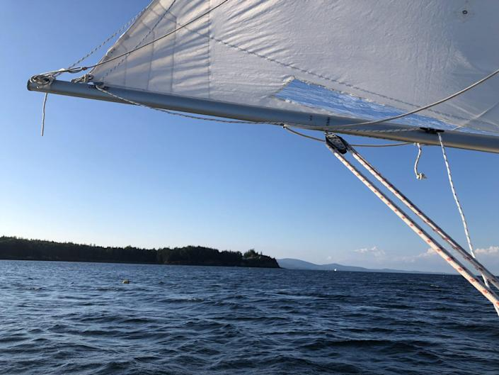 A view from the sailboat of a white sail and blue water