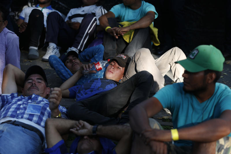 Scores of Central American migrants, representing the thousands participating in a caravan trying to reach the U.S. border, rest in front of the office of the United Nation's human rights body, after undertaking an hours-long march to demand buses, in Mexico City, Thursday, Nov. 8, 2018. Members of the caravan which has stopped in Mexico City demanded buses Thursday to take them to the U.S. border, saying it is too cold and dangerous to continue walking and hitchhiking.(AP Photo/Rebecca Blackwell)