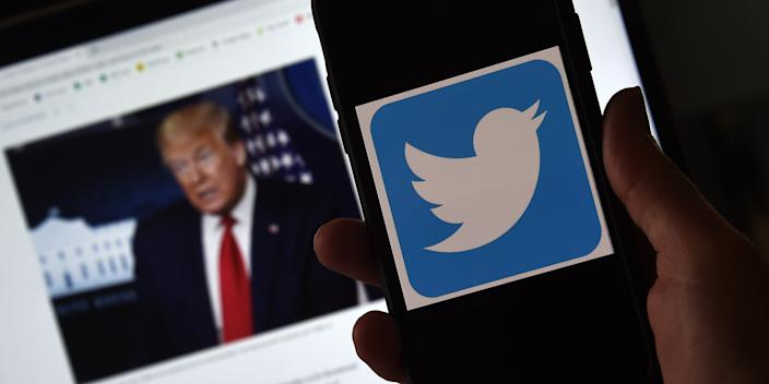 The Twitter logo on a mobile phone, with a photo of Trump on a computer in the background.
