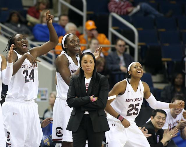 South Carolina players from left; forward Aleighsa Welch (24), center Alaina Coates (41) and Tiffany Mitchell (25) celebrate behind head coach Dawn Staley in the second half of a quarterfinal women's Southeastern Conference tournament NCAA college basketball game against Georgia Friday, March 7, 2014, in Duluth, Ga. South Carolina won 67-48. (AP Photo/Jason Getz)