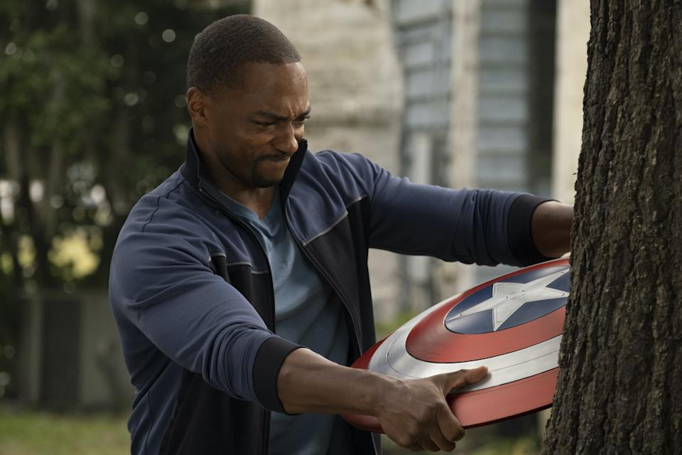 The Falcon (Anthony Mackie) pulls Captain America's shield from a tree in a scene from the TV series The Falcon and the Winter Soldier