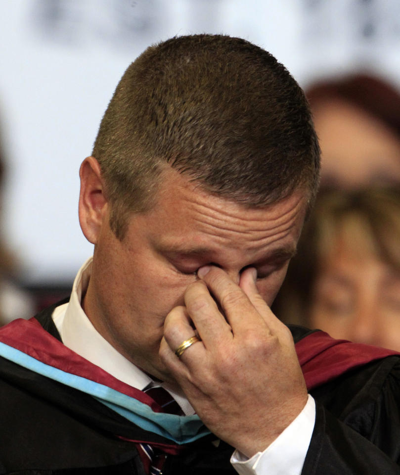 Joplin School Superintendent C.J. Huff wipes away tears as he addresses the Class of 2012 during Joplin High School commencement ceremonies Monday, May 21, 2012, in Joplin, Mo. Seniors at the school finished their high school education in a converted big-box store after the old high school was destroyed by an EF-5 tornado that killed 161 people on graduation day a year ago. (AP Photo/Charlie Riedel)