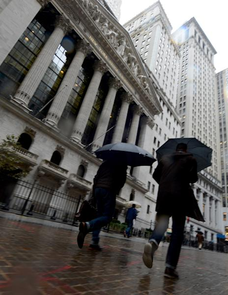 Pedestrians walk in the rain past the New York Stock Exchange the day after Pres. Barack Obama was re-elected, Wednesday, Nov. 7, 2012 in New York. (AP Photo/Henny Ray Abrams)