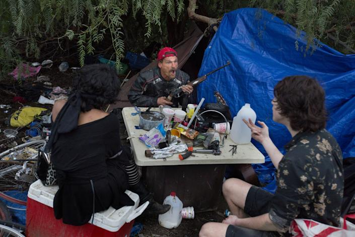 "Holding a BB rifle, Ron Clark, 53, gets animated during a discussion about Jesus Christ with two other people at a Sepulveda Basin homeless encampment in February 2017. Clark, who came to Los Angeles from Chicago, said he was psychologically and sexually abused as a child and became homeless when he ran away at 14. He was eventually kicked out of the encampment. <span class=""copyright"">(Ivan Kashinsky / For The Times)</span>"