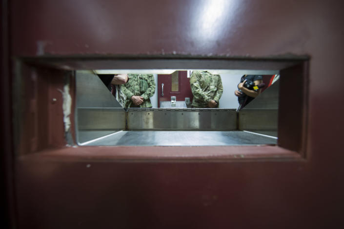 FILE - In this April 17, 2019, file photo reviewed by U.S. military officials, U.S. soldiers stand as seen through the splash guard opening in a cell door, inside the Camp V detention facility in Guantanamo Bay Naval Base, Cuba. The White House says it intends to shutter the prison on the U.S. base in Cuba, which opened in January 2002 and where most of the 39 men still held have never been charged with a crime. (AP Photo/Alex Brandon, File)