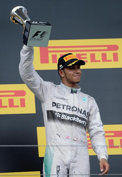 Mercedes driver Lewis Hamilton celebrates on the podium at the Hungarian Grand Prix in Budapest on July 27, 2014 (AFP Photo/Attila Kisbenedek)