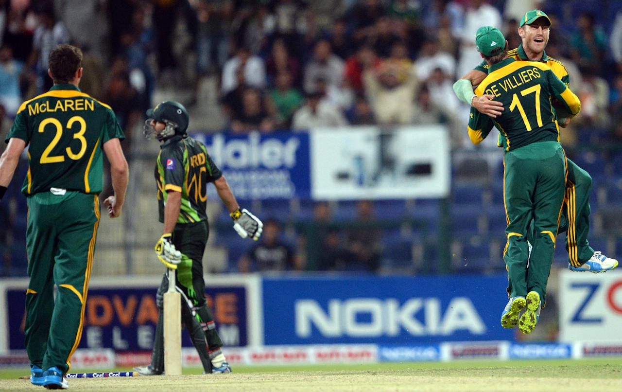 South African cricketer Morne Morkel (R) celebrates with his captain AB de Villiers (2nd R) after running out of Pakistani batsman Shahid Afridi (2nd L) during the fourth day-night international in Sheikh Zayed Cricket Stadium in Abu Dhabi on November 8, 2013. South Africa beat Pakistan by 28 runs, to take an unbeatable 3-1 lead in the five-match series. AFP PHOTO/ Asif HASSAN        (Photo credit should read ASIF HASSAN/AFP/Getty Images)