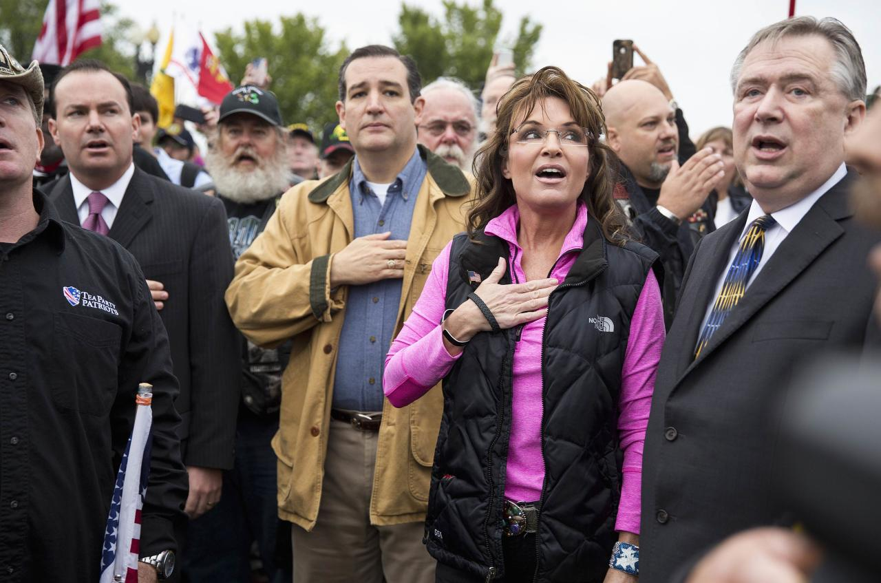 "Former Alaska Governor Sarah Palin and Senator Ted Cruz (C) (R-TX) recite the Pledge of Allegiance during the ""Million Vet March on the Memorials"" at the U.S. National World War II Memorial in Washington October 13, 2013. The group was organized in protest of to the Obama administration's decision to close the memorial and bar entry to World War Two vets who had traveled to visit it during the partial government shut down. REUTERS/Joshua Roberts (UNITED STATES - Tags: POLITICS BUSINESS EMPLOYMENT MILITARY CIVIL UNREST)"