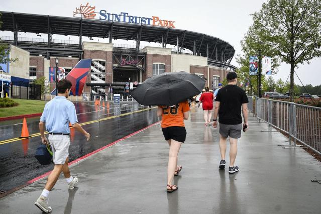 <p>Fans arrive at SunTrust Park for the Atlanta Braves' baseball game against the San Francisco Giants, June 20, 2017, in Atlanta. Tropical Storm Cindy has been causing rain in much of the Southeast. (Photo: John Amis/AP) </p>