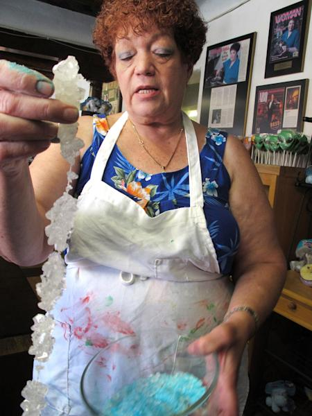 "FILE - In this Aug. 20, 2012 file photo, Debbie Ball, 60, owner of The Candy Lady store in Albuquerque, N.M., displays her new line of ""meth candy"" made from sugar rock candy. The store supplied some of its ""meth candy"" to be used as a prop for the blue crystal meth on the TV hit series ""Breaking Bad."" As ""Breaking Bad"" finishes filming its fifth and final season in Albuquerque, the popularity of the show is providing a boost to the economy and creating a dilemma for local tourism officials as they walk the fine line of profiting from a show that centers around drug trafficking, addiction and violence. (AP Photo/Russell Contreras, File)"