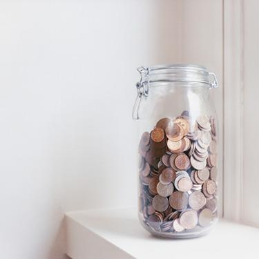Glass-jar-filled-with-coins-on-a-windowsill_web