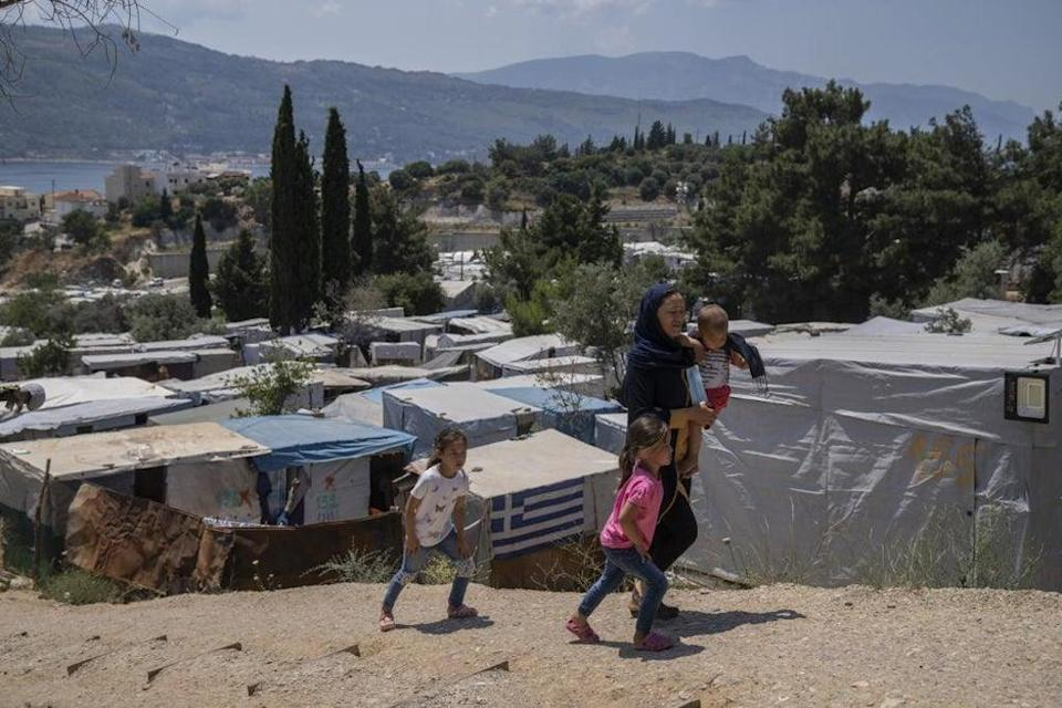 An Afghan woman with her three children walk outside the perimeter of the refugee camp at the port of Vathy on the eastern Aegean island of Samos, Greece, on Friday, 11 June  (AP)