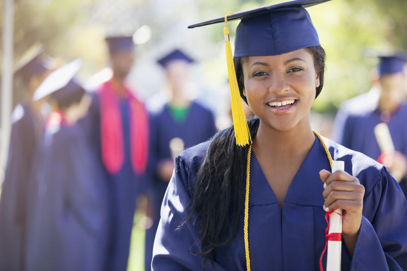 Young woman in cap and gown holding diploma, with others in cap and gown in the background