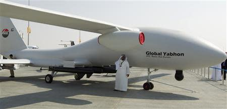 A visitor speaks on his phone in the shade of unmanned drone during the Dubai Airshow