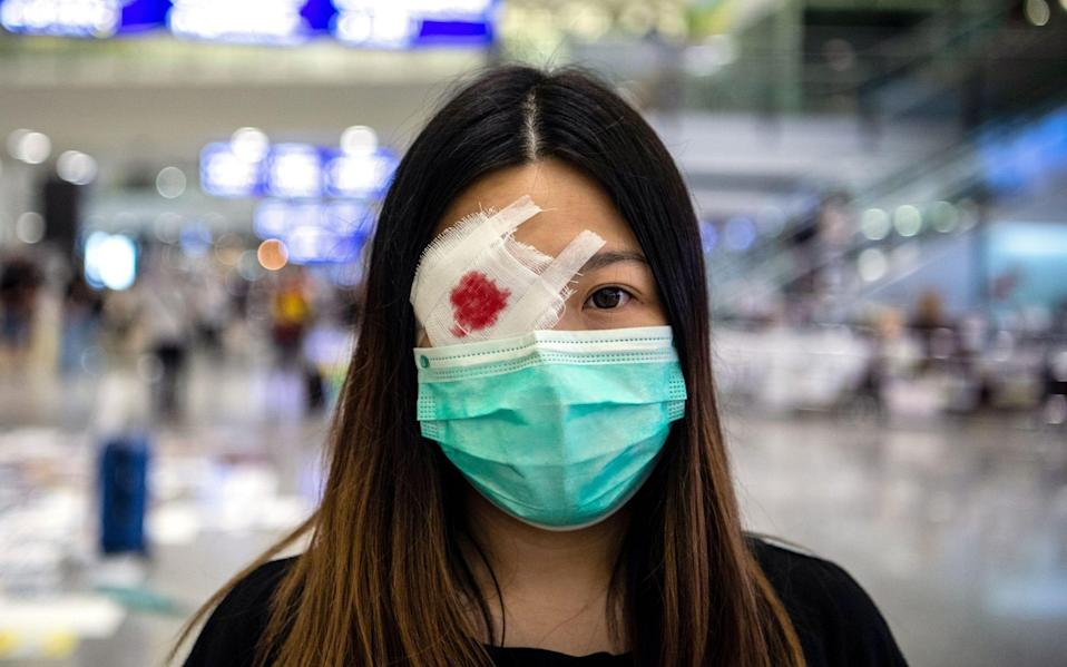 A protester wears a mock eye patch during the occupation of Hong Kong International Airport - REX