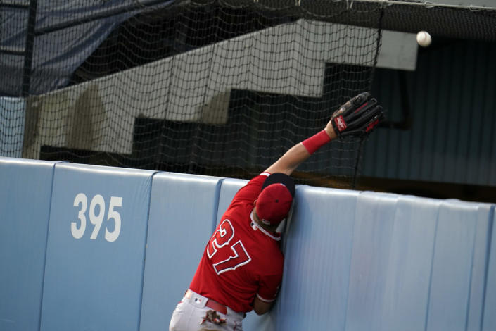 Los Angeles Angels center fielder Mike Trout (27) leaps but can't catch a home run ball from Los Angeles Dodgers' Mookie Betts during the first inning of a spring training exhibition baseball game Tuesday, March 30, 2021, in Los Angeles. (AP Photo/Marcio Jose Sanchez)