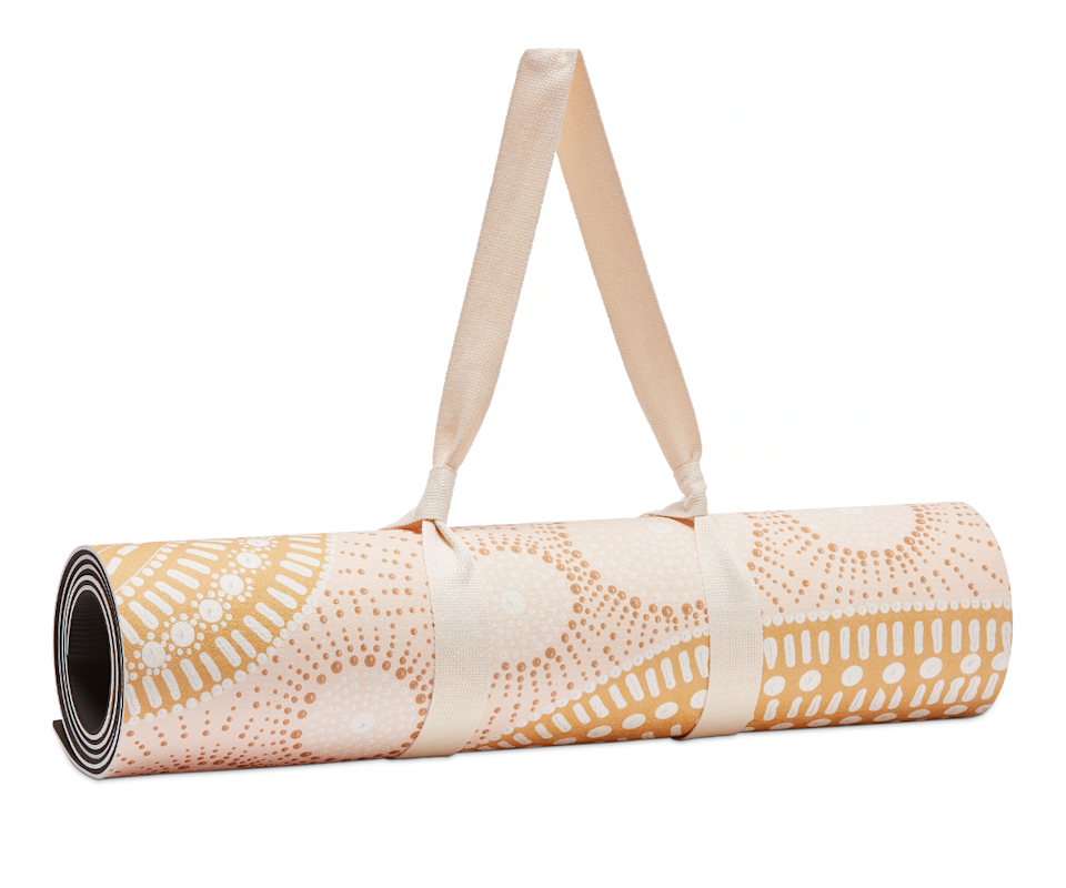 A rolled yoga mat in a pale pink and orange pastel indigenous pattern.