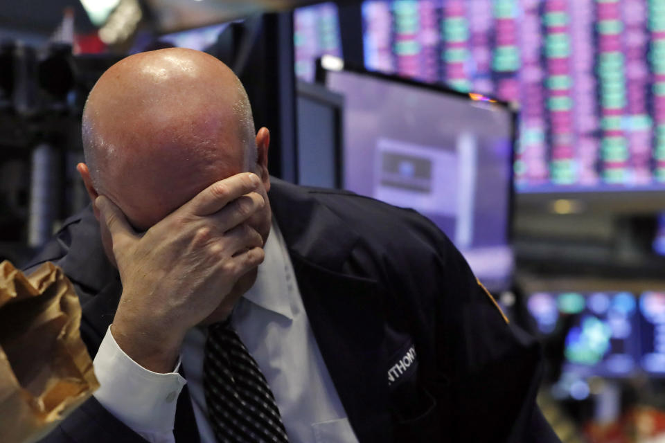 A trader has his head in his hand on the floor of the New York Stock Exchange, Thursday, March 12, 2020. (AP Photo/Richard Drew)