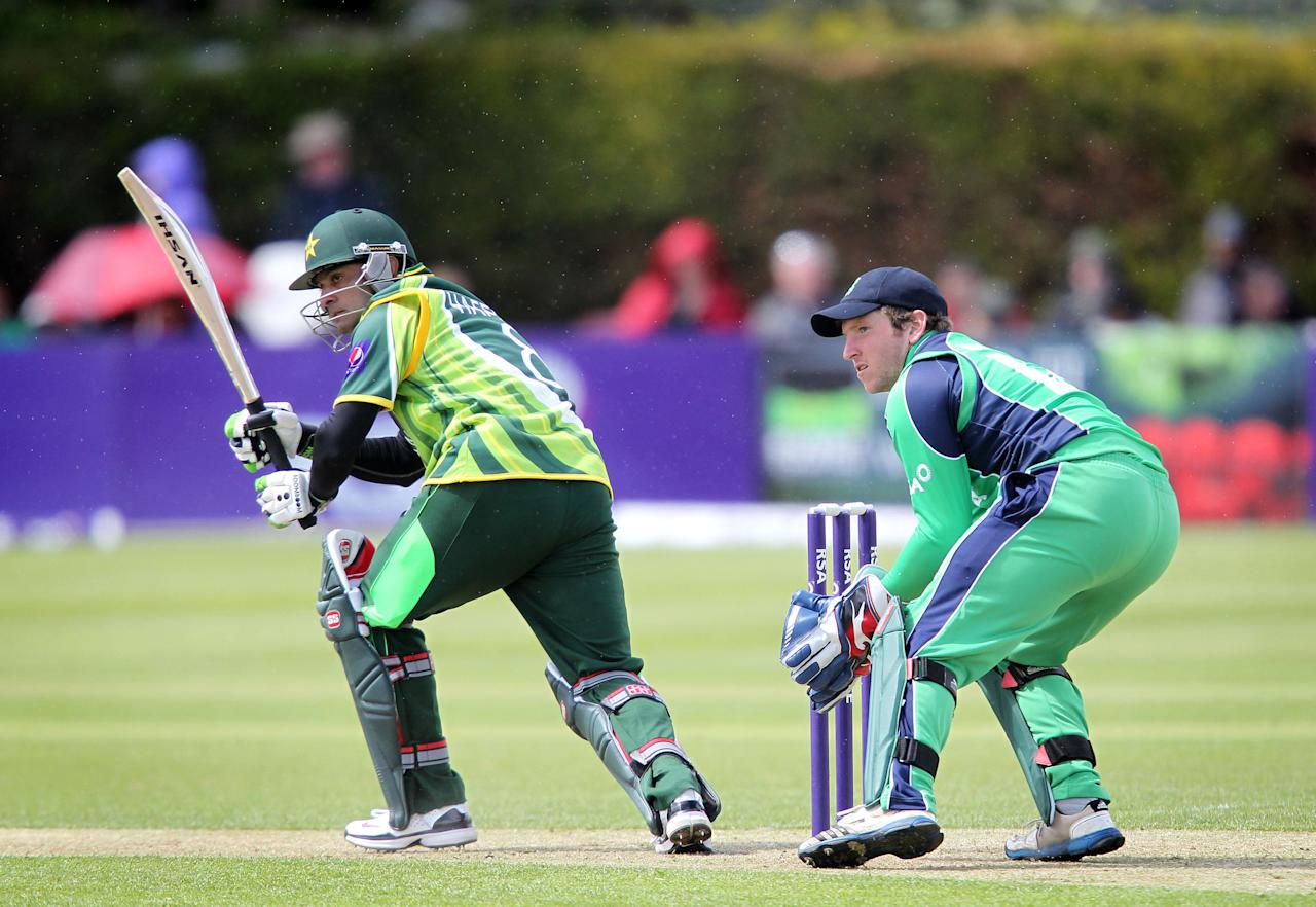 Pakistan's Mohammad Hafeez (L) bats as Ireland's wicketkeeper Gary Wilson (R) looks on during the One Day International (ODI) cricket match between Pakistan and Ireland at Clontarf Cricket Club in Dublin on May 23, 2013.