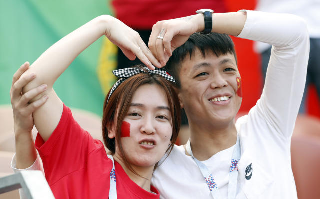 FILE - In this Wednesday, June 20, 2018 file photo, soccer fans from China pose for a photograph prior to the group B match between Portugal and Morocco at the 2018 soccer World Cup at the Luzhniki Stadium in Moscow, Russia, Wednesday, June 20, 2018. Chinese sponsors are more visible than ever and tens of thousands of Chinese fans have descended on Moscow, using their growing economic clout to secure top-dollar seats and dreaming of the day, perhaps not that far off, when China will host football's showcase. (AP Photo/Antonio Calanni, File)