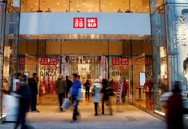 FILE PHOTO: People walk past Japan's Fast Retailing Co Ltd's Uniqlo signboard at its shop in Tokyo