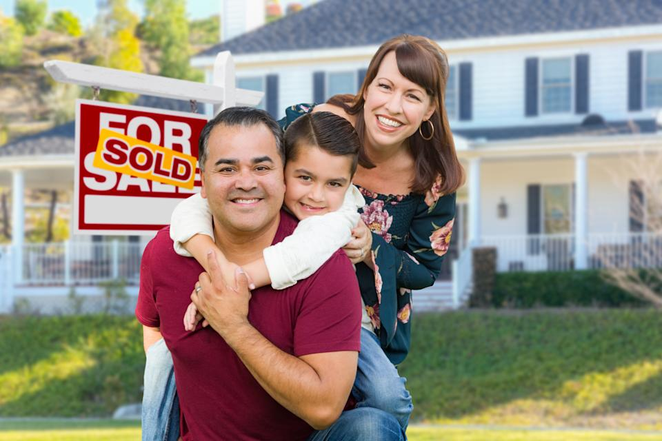 Happy Family In Front of House and Sold For Sale Real Estate Sign.
