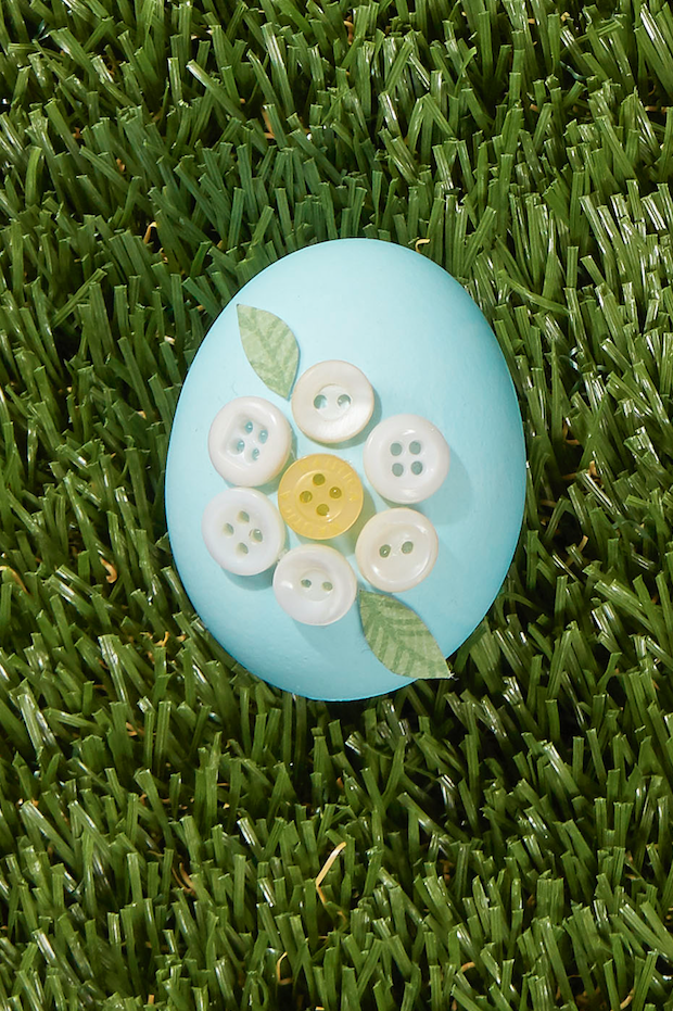 "<p>Hot-glue small white and yellow buttons, arranged in a flower shape, to a natural or dyed egg to achieve this pretty look. Attach paper leaves with hot glue to finish it off.</p><p><a class=""link rapid-noclick-resp"" href=""https://www.amazon.com/Assorted-Childrens-Painting-Handmade-Ornament/dp/B076FLR6X1?tag=syn-yahoo-20&ascsubtag=%5Bartid%7C10050.g.1282%5Bsrc%7Cyahoo-us"" rel=""nofollow noopener"" target=""_blank"" data-ylk=""slk:SHOP BUTTONS"">SHOP BUTTONS</a></p>"