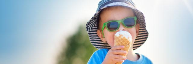 Happy child eating ice cream outdoors in summer.