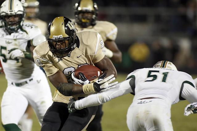 Central Florida running back William Stanback (28) avoids the tackle of South Florida linebacker Tashon Whitehurst (51) during the first half of an NCAA college football game Friday, Nov. 29, 2013, in Orlando, Fla. (AP Photo/Reinhold Matay