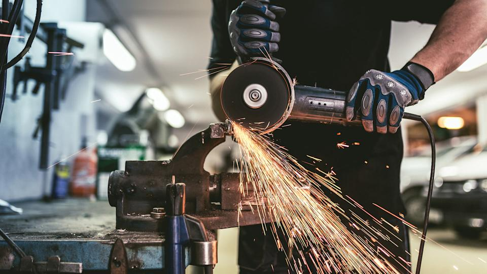 Heavy industry worker cutting steel with an angle grinder.