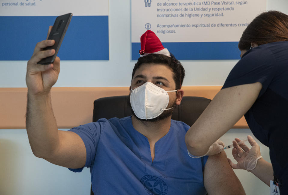ICU Dr. German Osorio takes a selfie as he gets his COVID-19 vaccine shot at the Posta Central Hospital in Santiago, Chile, Thursday, Dec. 24, 2020, on the same day the first shipment of vaccines arrived from Pfizer and its German partner, BioNTech. (AP Photo/Esteban Felix)