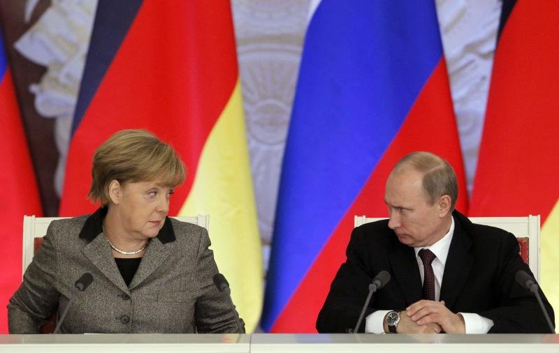 Russian President Vladimir Putin (R) and German Chancellor Angela Merkel look at each other while answering journalists' questions during a joint news conference in Moscow's Kremlin, in this November 16, 2012 file photo. Heavily dependent on Russian gas and closer to Moscow than any other leading western nation, Germany faces a major policy dilemma as the Ukraine crisis descends into a Cold War-style confrontation of tit-for-tat threats and ultimatums. For weeks, Merkel and her three-month old coalition government have gone out of their way to avoid antagonising Putin, remaining measured even as Washington and other capitals ratcheted up the rhetoric. REUTERS/Maxim Shemetov/Files (RUSSIA - Tags: POLITICS)