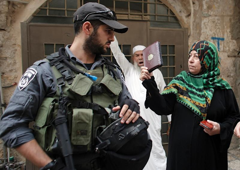 A Palestinian woman holds a copy of the Koran as she confronts an Israeli soldier outside the Al-Aqsa mosques compound in Jerusalem's Old City, on September 10, 2015 (AFP Photo/Ahmad Gharabli)