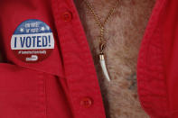 """Ramon Silva, 78, wears an """"I voted"""" sticker, as he passes the time in Little Havana after casting his ballot in early voting, in Miami, Wednesday, Oct. 28, 2020. Silva, who said he was a political prisoner in Cuba for 15 years before coming to the U.S. 41 years ago, voted for President Donald Trump because he fears any shift toward socialism in his adopted homeland. (AP Photo/Rebecca Blackwell)"""