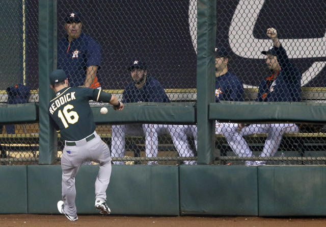Oakland Athletics right fielder Josh Reddick (16) chases the ball to the wall in front of the Houston Astros bullpen on Astros' Jonathan Villar's double in the third inning of a baseball game on Friday, April 25, 2014, in Houston. (AP Photo/Pat Sullivan)