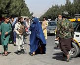FILE PHOTO: Taliban forces block the roads around the airport, while a woman with Burqa walks passes by, in Kabul