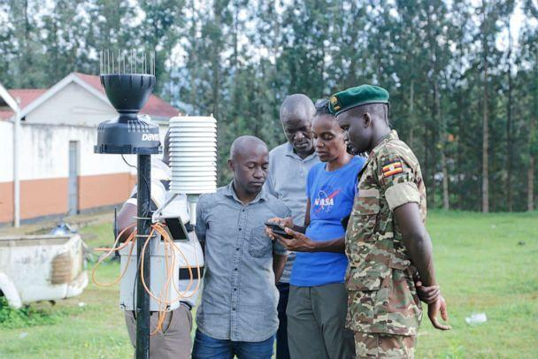 PHOTO: Dr. Catherine Nakalembe demonstrates field data collection with local officials and government staff in Uganda. (Raphael Luhahe)