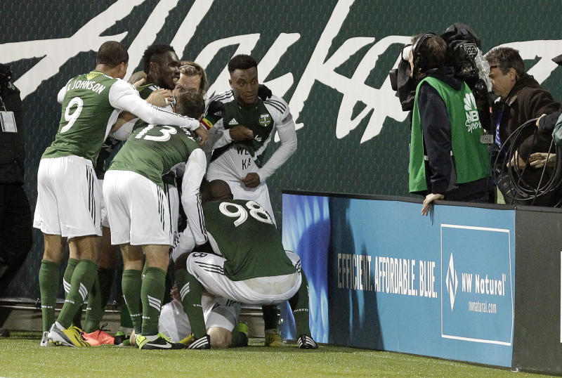 Portland Timbers players pose for the television camera at right as they celebrate scoring on a penalty kick during the second half of an MLS soccer game against the San Jose Earthquake in Portland, Ore., Sunday, April 14, 2013. Portland won 1-0.(AP Photo/Don Ryan)