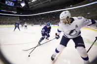 Toronto Maple Leafs center William Nylander (88) and Tampa Bay Lightning center Alex Killorn (17) reach for the puck in the corner during the second period of an NHL hockey game Thursday, Oct. 10, 2019, in Toronto. (Cole Burston/The Canadian Press via AP)