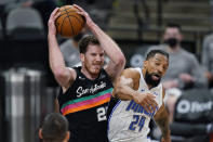 San Antonio Spurs center Jakob Poeltl (25) pulls down a rebound over Orlando Magic center Khem Birch (24) during the first half of an NBA basketball game in San Antonio, Friday, March 12, 2021. (AP Photo/Eric Gay)