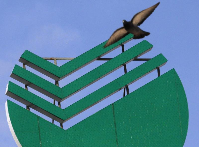A bird flies near a Sberbank sign placed on the roof of a building in St. Petersburg